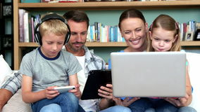 Cute family using technologies sitting on the couch stock video