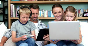Cute family using technologies sitting on the couch stock video footage