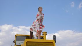 Cute Farm girl in dress to bonnet of tractor on background of blue sky. Cute Farm girl in long dress to bonnet of yellow tractor on nature on background of blue stock footage