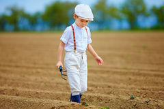 Cute farmer boy walking the arable field. S Stock Photo
