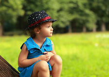 Cute fashion clothing kid girl sitting on tree Stock Images