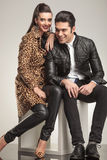 Cute fashion couple smiling while sitting on a white cube Royalty Free Stock Photo