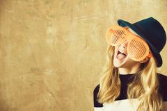 Cute fashion happy girl with funny glasses and green hat stock photography
