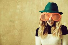 Cute fashion happy girl with funny glasses and green hat stock image