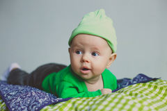 Cute fashion hipster baby in green hat. Cute fashion hipster baby boy in green hat looking seriously royalty free stock photo