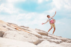 Cute fashion man dancing on the rock and feel freedom. Young fashion man dancing on the rock and feel freedom on a blue sky background Royalty Free Stock Photography