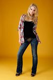 Cute fashion teen. Teen model poses wearing tank top with unbuttoned shirt and jeans Stock Photo