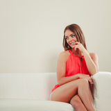 Cute fashion woman in red shirt on sofa couch. Royalty Free Stock Photos