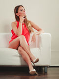 Cute fashion woman in red shirt on sofa couch. Royalty Free Stock Photography