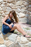 Cute fashion woman sitting on the edge of the wall Royalty Free Stock Images