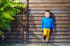 Cute fashionable boy in front of wooden wall Stock Photography
