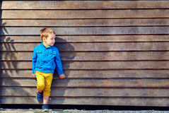 Cute fashionable boy in front of wooden wall Stock Images