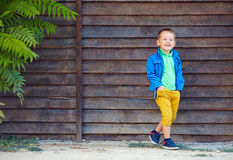 Cute fashionable boy in front of wooden wall Stock Image