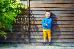 Cute fashionable boy in front of wooden wall Royalty Free Stock Images
