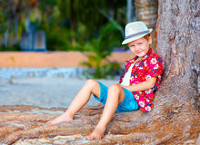Cute fashionable boy near the tree on the beach Royalty Free Stock Images