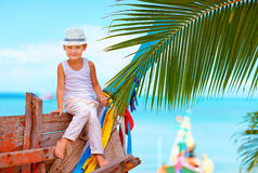 Cute fashionable boy posing on old boat at tropical beach Royalty Free Stock Image