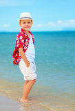 Cute fashionable boy stands in surf on summer beach Stock Image