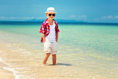Cute fashionable boy stands in surf on summer beach. Cute fashionable boy stands in surf on summer sand  beach Royalty Free Stock Images
