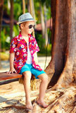 Cute fashionable boy on swings at the beach Stock Photo