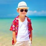 Cute fashionable boy walking on summer beach Stock Image