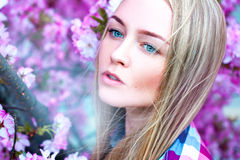 Cute fashionable girl near pink flowers Royalty Free Stock Photography
