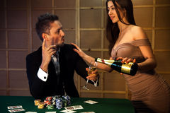Cute fashionable guy flirting with a lady who pours champagne at Royalty Free Stock Photography