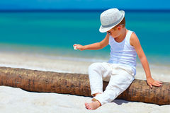 Cute fashionable kid, boy playing with shell on tropical beach. Cute fashionable kid, boy playing with shell on tropical sand beach Royalty Free Stock Photo