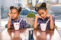 Cute fashionable sisters wearing nice bright bracelets feeling bored stock photos
