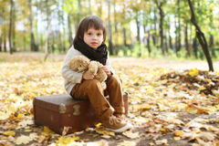 Cute fashionably dressed boy sitting on suitcase in the autumn p Stock Photos