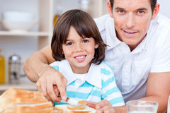 Cute father and his son spreading jam on bread Stock Images