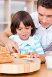 Cute father and his son spreading jam on bread Stock Photos