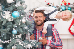 Cute father and son are decorating New Year tree. Cheerful young men and his child are preparing Christmas tree for celebration. The parent is holding a boy on royalty free stock image