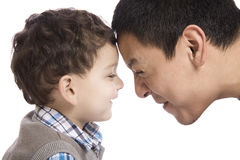 Cute father and son embracing, family relationship. A cute father and son forehead to forehead on studio white background stock photo
