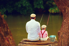 Cute father and son fishing together among beautiful pristine nature. Rear view Royalty Free Stock Photo