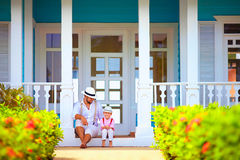 Cute father and son sitting on porch, caribbean exterior Stock Image