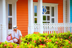 Cute father and son sitting and talking on porch, caribbean street Royalty Free Stock Image