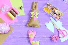 Cute felt Easter bunny with hearts decor. Craft supplies on a wooden background. Creative bunny wall decor Stock Images
