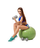 Cute female athlete exercising with dumbbells Royalty Free Stock Image