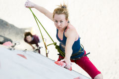 Cute female Athlete hanging on climbing Wall holding Rope Stock Photography