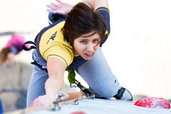 Cute female Athlete hanging on climbing Wall Stock Images