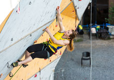 Cute female Athlete hanging on climbing Wall Stock Photos