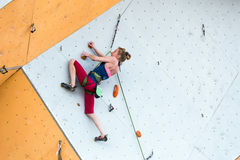 Cute female Athlete hanging on climbing Wall Royalty Free Stock Photo