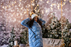 Cute female in blue down jacket standing near a swing and puttin. G on a white knitted warm hat in a snow-covered park with spruce tree, wearing woolen sweater Royalty Free Stock Images