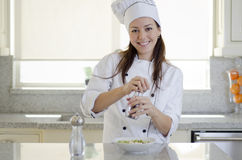 Cute female chef adding pepper Stock Photos