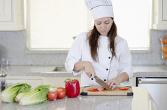 Cute female chef making a salad. Portrait of a young female chef cutting some vegetables for a salad Stock Photos