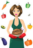 Cute Female Chef With Roasted Turkey Against Set of Vegetables. Attractive female chef in green dress and red oven mittens holding a roasted turkey (chicken) Stock Images