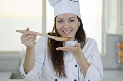 Cute female chef tasting soup. Portrait of a young female chef cooking dinner and tasting the soup Stock Image