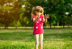 Cute female child catches soap bubbles in nature royalty free stock image