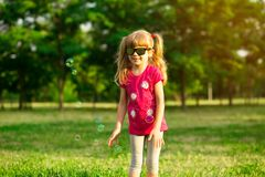 Cute female child catches soap bubbles in nature stock photography