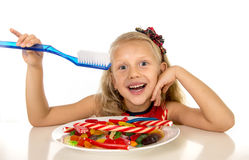 Cute female child eating dish full of sweets and holding huge toothbrush in dental care and health concept. And unhealthy sugar abuse isolated on white Royalty Free Stock Photos